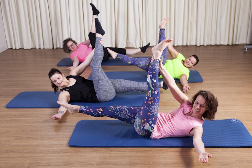 Bedrijfsreportage foto voor yogastudio waarbij meerdere mensen een yoga oefening uitbeelden. Martijn Voorhout Fotografie